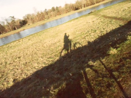 shadow of a bicycle with river in the background all at an agle upwards